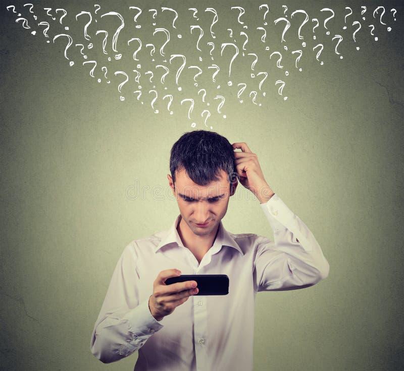 De verwarde mens die zijn mobiele slimme telefoon bekijken heeft vele vragen stock afbeeldingen