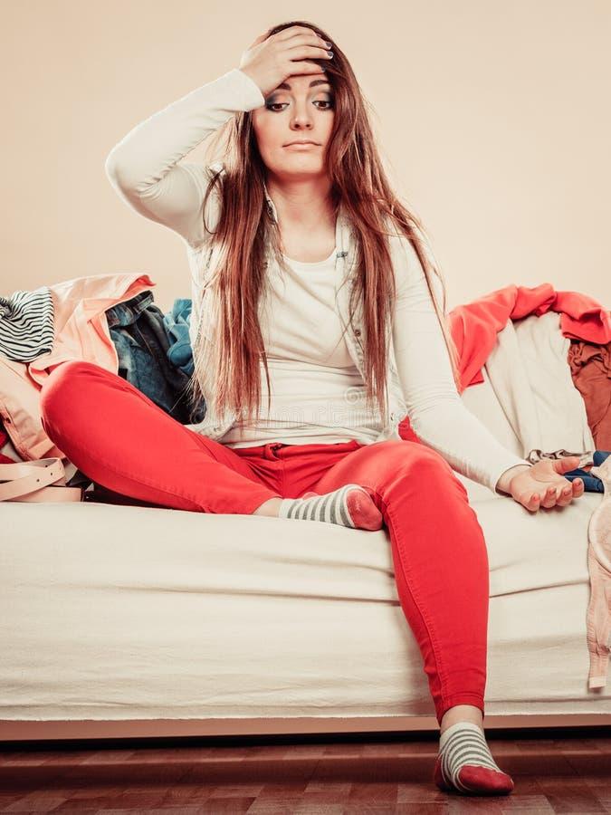 De verwarde vrouw zit op bankhoogtepunt van kleren stock afbeelding