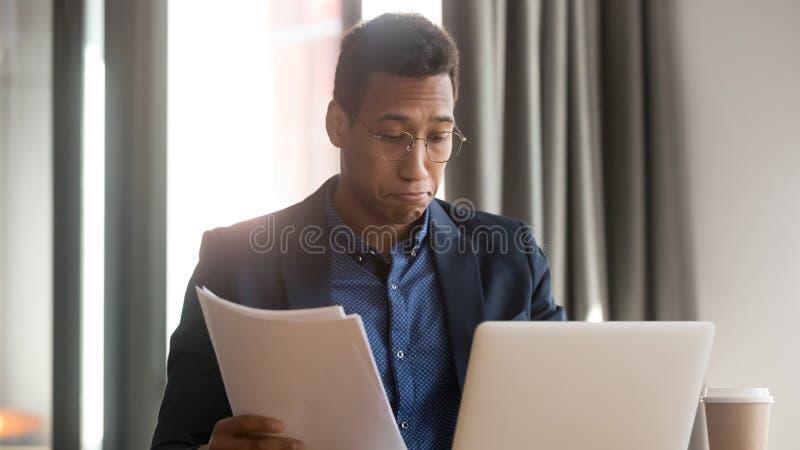 De verwarde zwarte mannelijke werknemer voelt de onzekere documenten van de lezingsadministratie stock fotografie