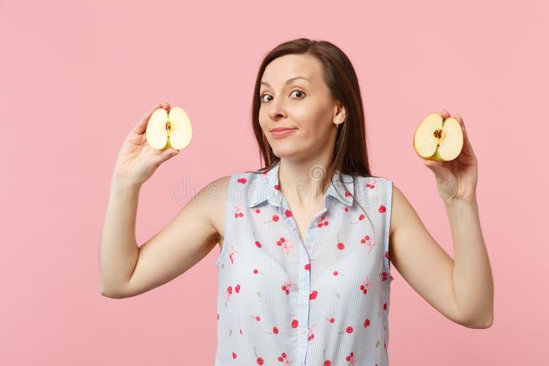 De in verwarring gebrachte jonge vrouw in de zomer kleedt het houden in handen halfs van vers rijp die appelfruit op roze pastelk royalty-vrije stock foto's