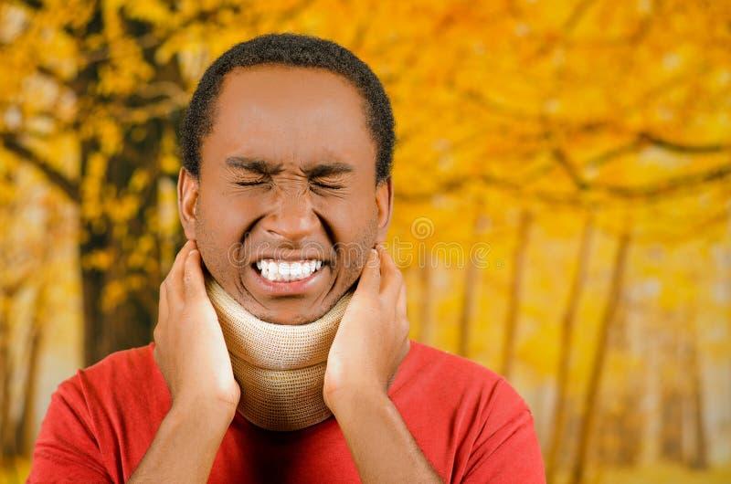 De verwonde jonge positieve zwarte Spaanse mannelijke dragende halssteun, het houden dient pijn rond steun in die gezichten maken stock foto's
