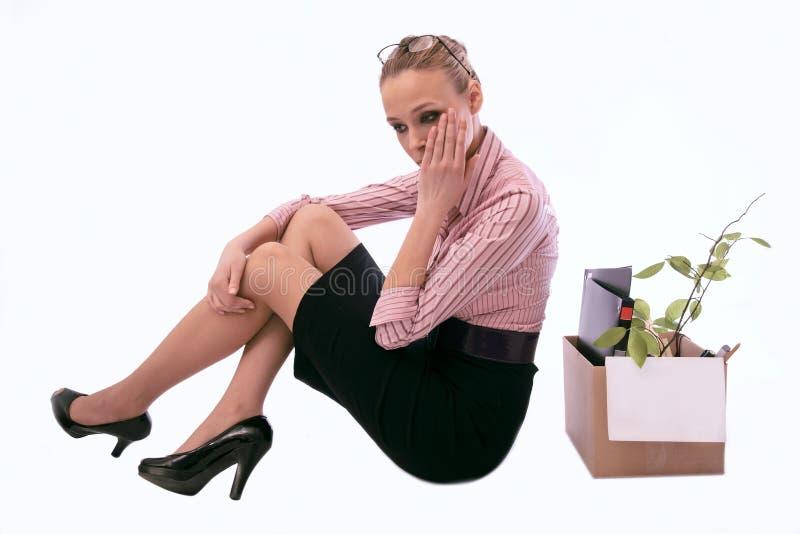 De verworpen werkende vrouw met een doos in zorg stock afbeeldingen