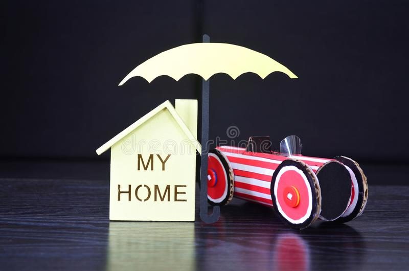 De verzekering, een paraplu beschermt huis en auto stock afbeelding