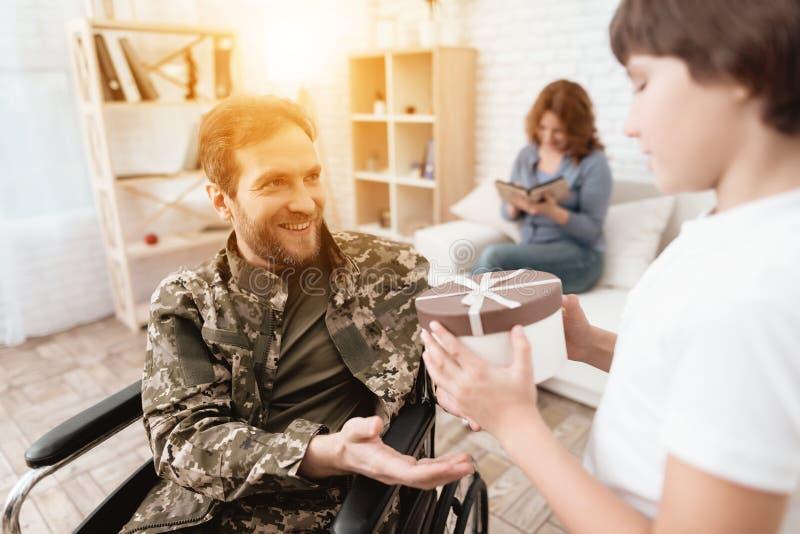 De veteraan in een rolstoel kwam van het leger terug Een mens in eenvormig in een rolstoel met zijn familie stock afbeeldingen