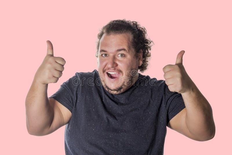 De vette gelukkige mens toont de duim omhoog op witte achtergrond ondertekent royalty-vrije stock afbeeldingen