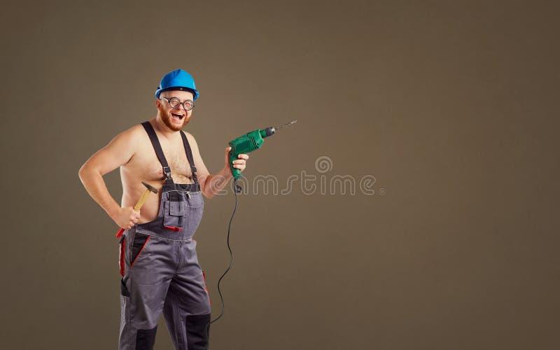 De vette grappige mensenbouwer met een boor stock fotografie