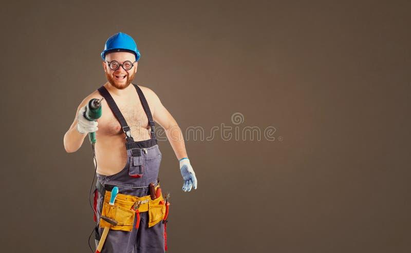 De vette grappige mensenbouwer met een boor stock afbeeldingen