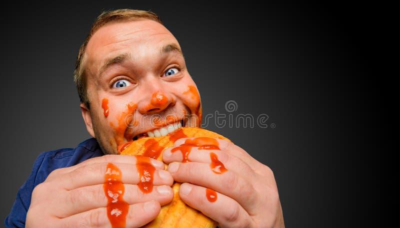 De vette mens bijt de smakelijke paninisandwich royalty-vrije stock afbeeldingen