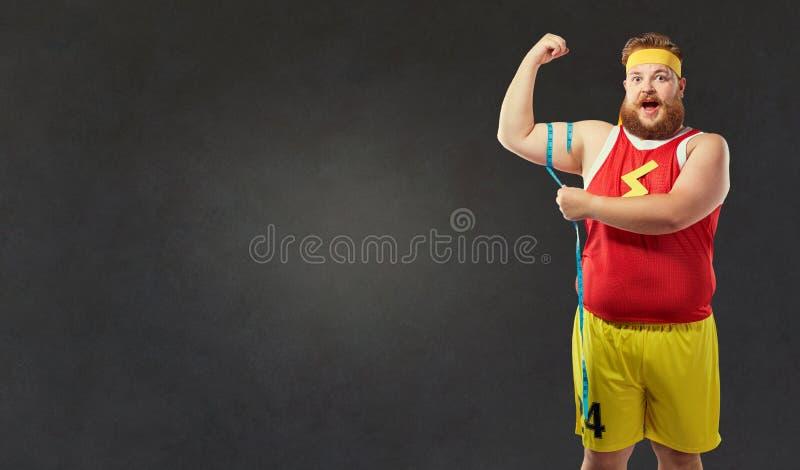 De vette mens in sportenkleren meet zijn wapen met een centim royalty-vrije stock afbeelding