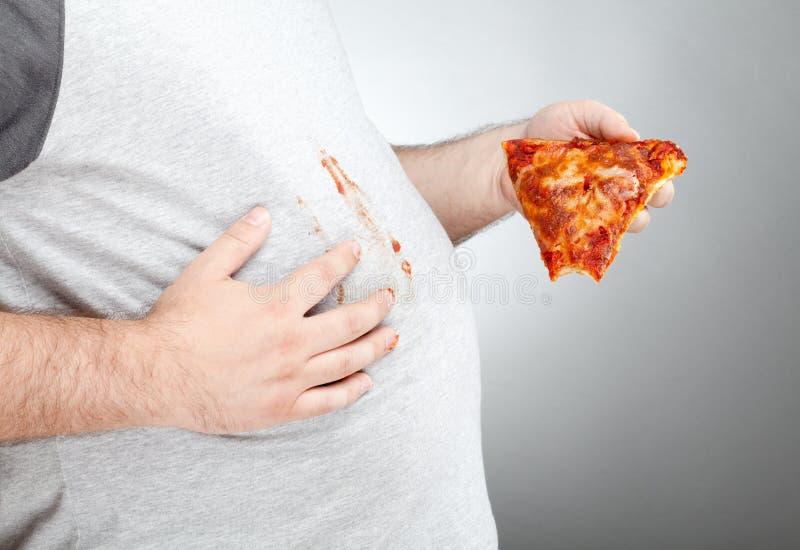 De vette saus van de mensen afvegende pizza op zijn overhemd royalty-vrije stock afbeelding