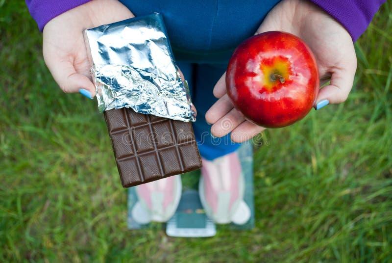 De vette vrouw bevindt zich op schalen en selecteert rode grote appel of chocoladereep in folie royalty-vrije stock foto's