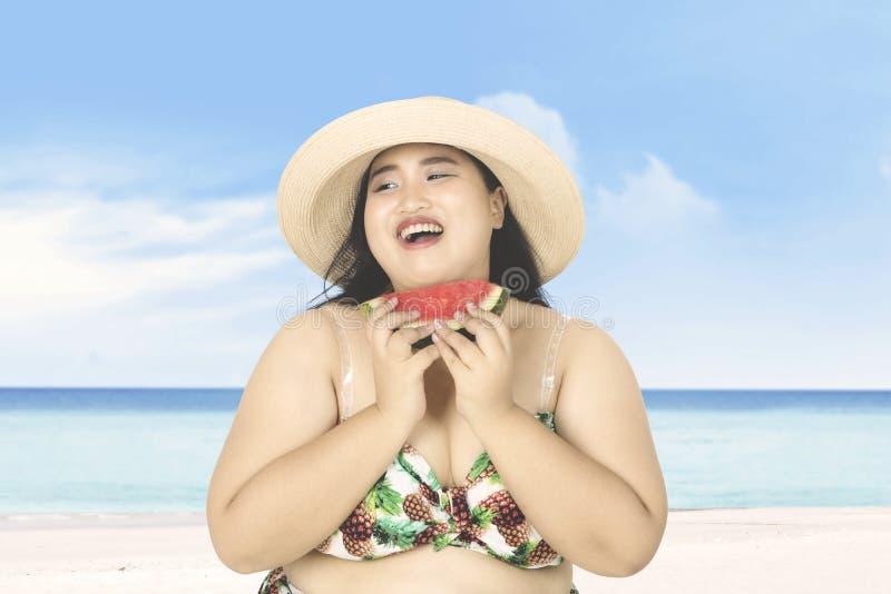 De vette vrouw eet watermeloen op strand stock foto