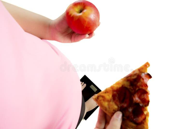 De vette vrouw houdt een appel en een pizza royalty-vrije stock afbeeldingen
