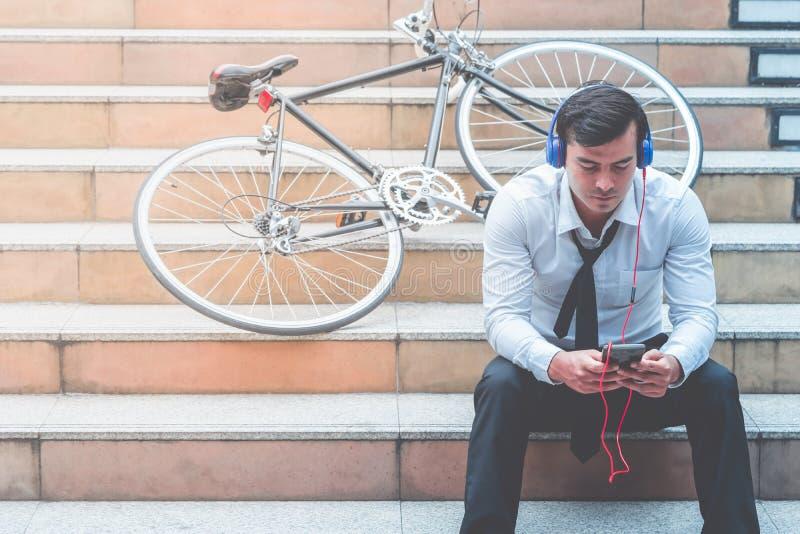 De Video van het bedrijfsmensenhorloge op mobiel met zijn fiets aan de kant stock afbeeldingen