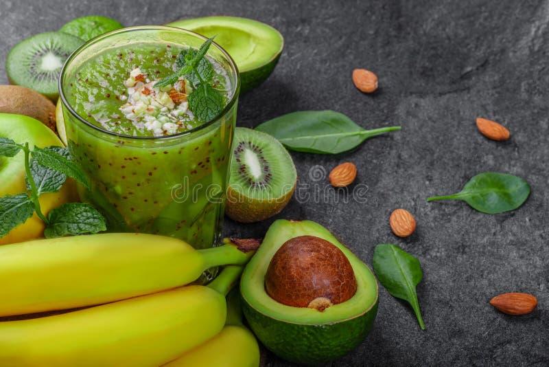 De vidro completamente do suco, de quivis, de bananas e de abacates verdes em um fundo de pedra da tabela Close-up de frutos trop imagem de stock