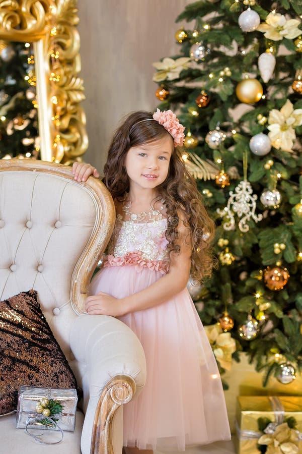 De Viering van Kerstmis Leuk meisje in een mooie kledingszitting dichtbij de Kerstboom Kerstmismirakelen Luxueuze Christus stock fotografie