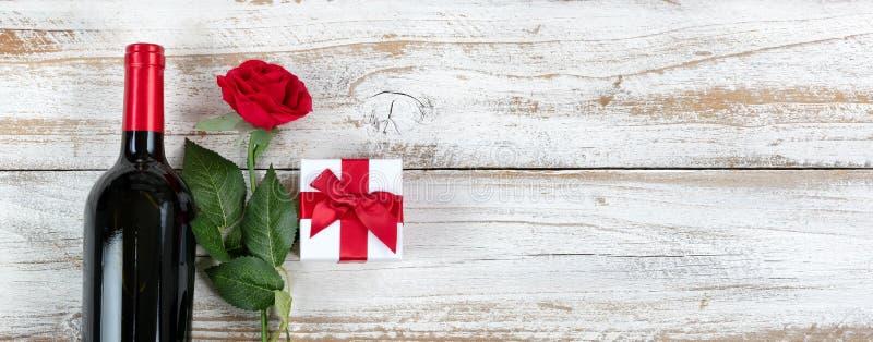 De viering van de valentijnskaartendag met rode wijn en de giften namen op wit rustiek hout toe royalty-vrije stock fotografie