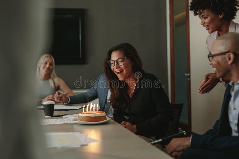 De viering van de verrassingsverjaardag van een vrouwelijke vennoot in bureau royalty-vrije stock fotografie