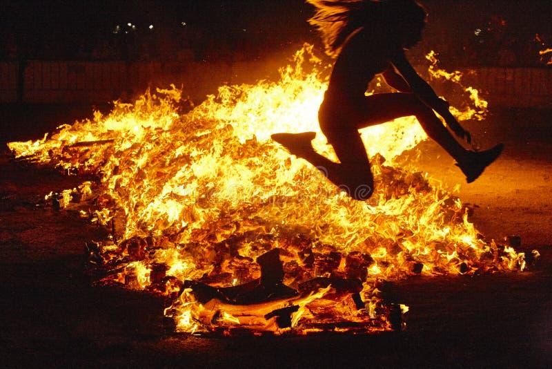 De viering van de de zomerzonnestilstand in Spanje De sprong van de vrouw Muur van vlammen stock fotografie