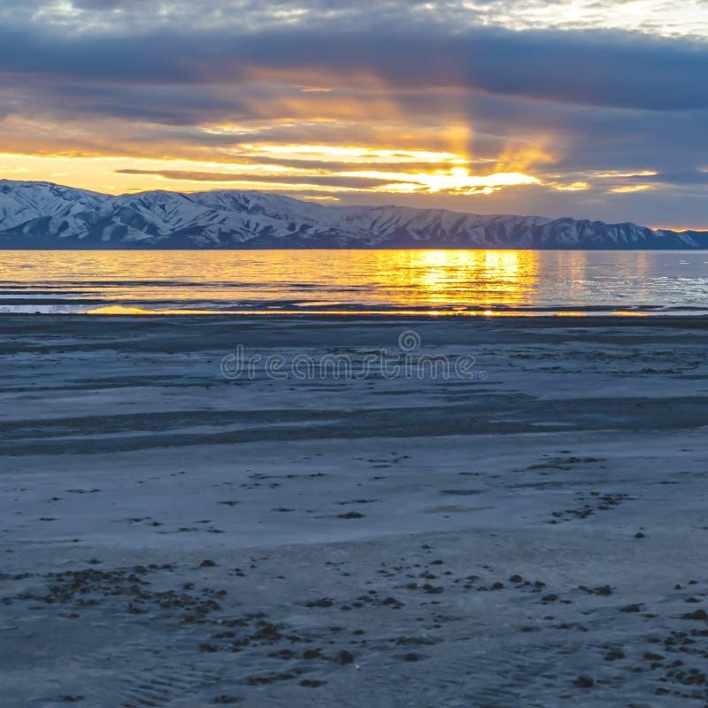 De vierkante kader Gouden zon overdacht het glinsterende meer met zandige kust bij zonsondergang stock foto