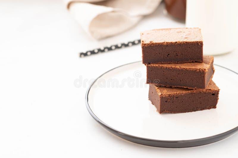 De vierkante stukken van de chocoladebrownie in stapel op witte plaat Amerikaans traditioneel heerlijk dessert De ruimte van het  stock afbeelding
