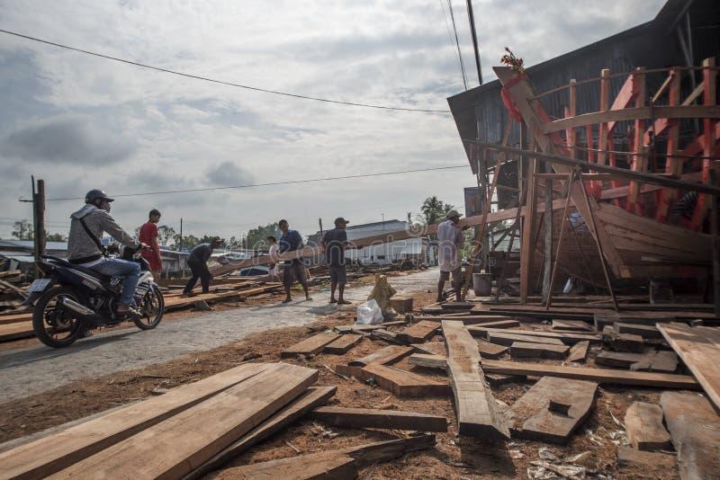 De Vietnamese arbeiders bouwen een grote houten boot in Nga-Baai in zuidelijk Vietnam royalty-vrije stock foto