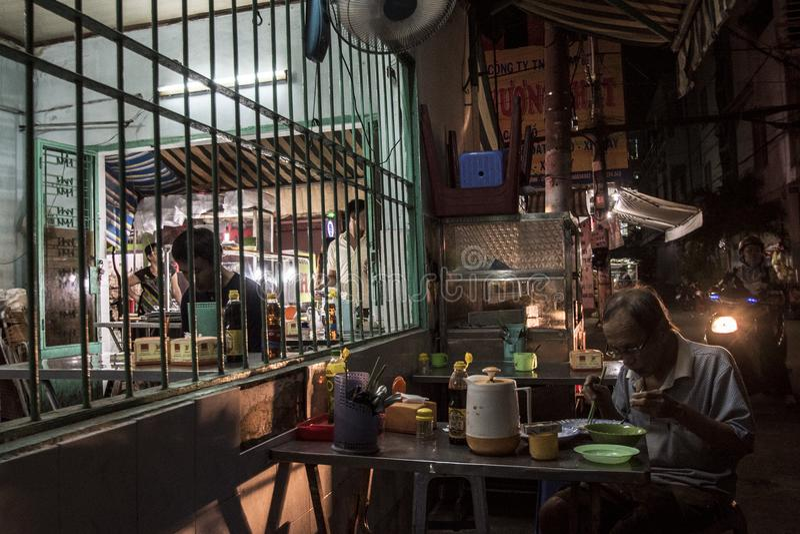 De Vietnamese hogere mens eet een noedelsoep bij een restaurant in een straat van Ho Chi Minh City, Vietnam stock afbeeldingen