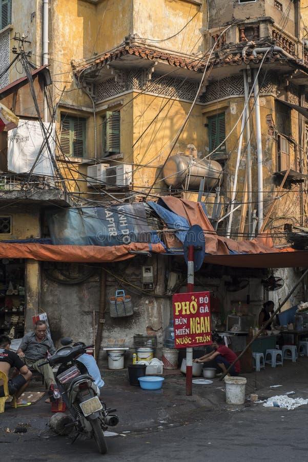 De Vietnamese ingezetenen genieten van een stil ogenblik op de straat door een oud geel gebouw in Hanoi, Vietnam stock afbeeldingen