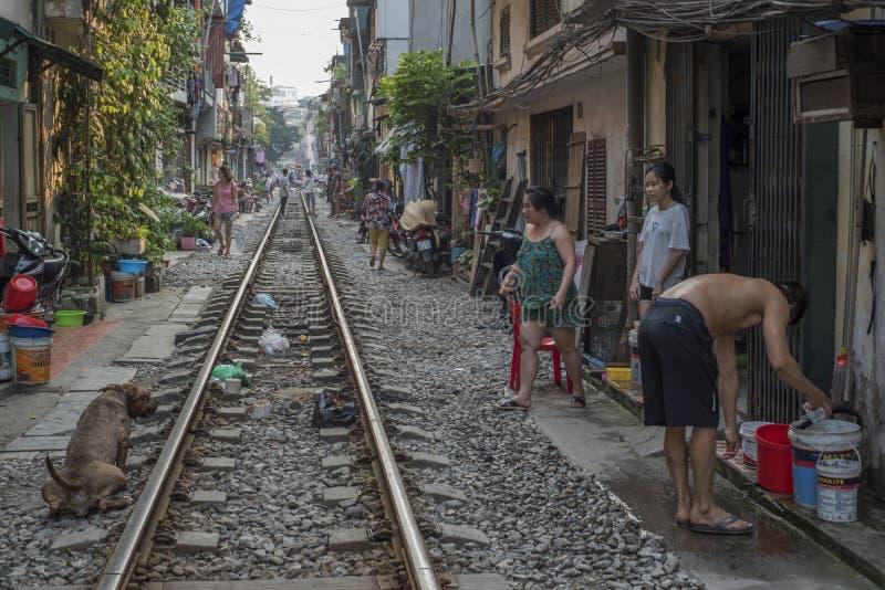De Vietnamese plaatselijke bewoners genieten van hun leven door de sporen in een uiterst kleine straat van Ha Noi, Vietnam royalty-vrije stock foto