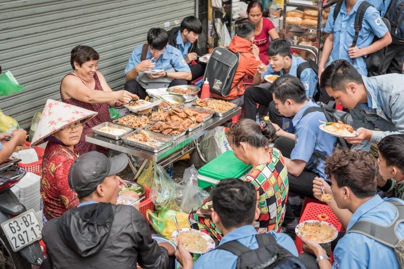 De Vietnamese studenten eten in de straat stock fotografie
