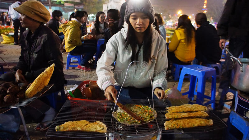 De Vietnamese verkoper van het straatvoedsel bij nacht openluchtmarkt royalty-vrije stock afbeelding