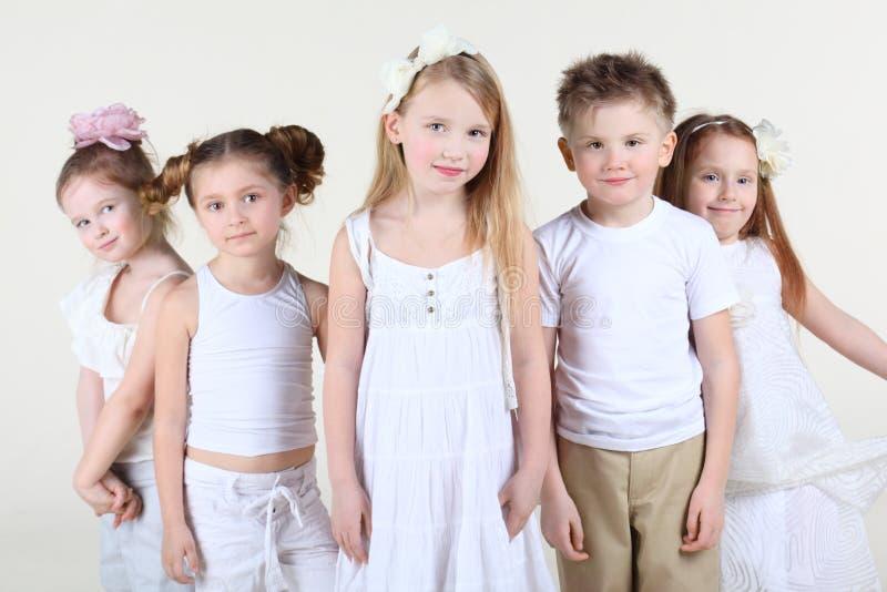 De vijf het glimlachen kinderentribune en bekijkt camera. royalty-vrije stock foto's