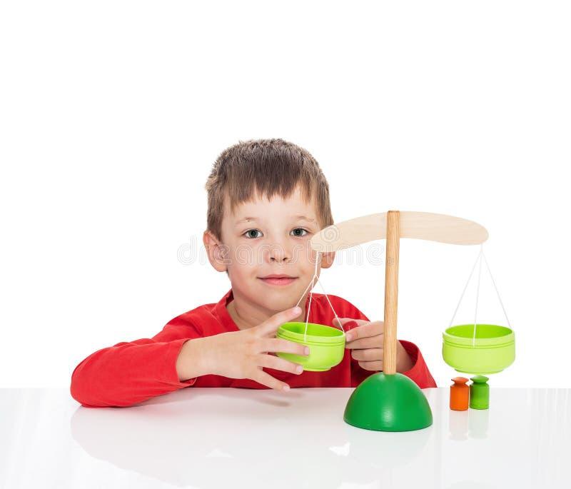 De vijf-jaar-oude jongen zit bij een witte lijst en speelt met houten schalen stock fotografie