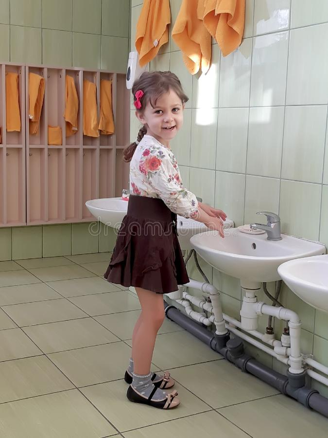 De vijf-jaar-oude meisjeswassen dient het wasbassin van kleuterschool in royalty-vrije stock foto's