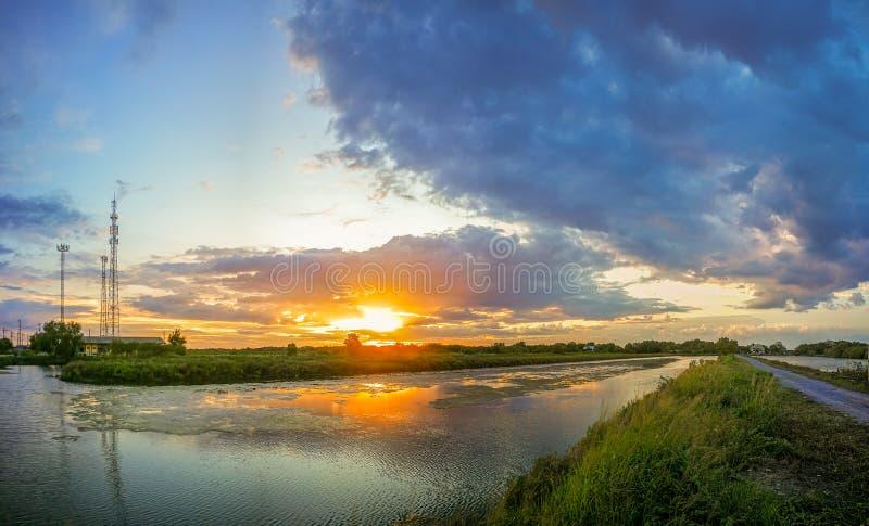 De vijver wijst op het licht van de oranje zon De poolrand is groen en geel gras De avondhemel vóór de zonsondergang is royalty-vrije stock foto