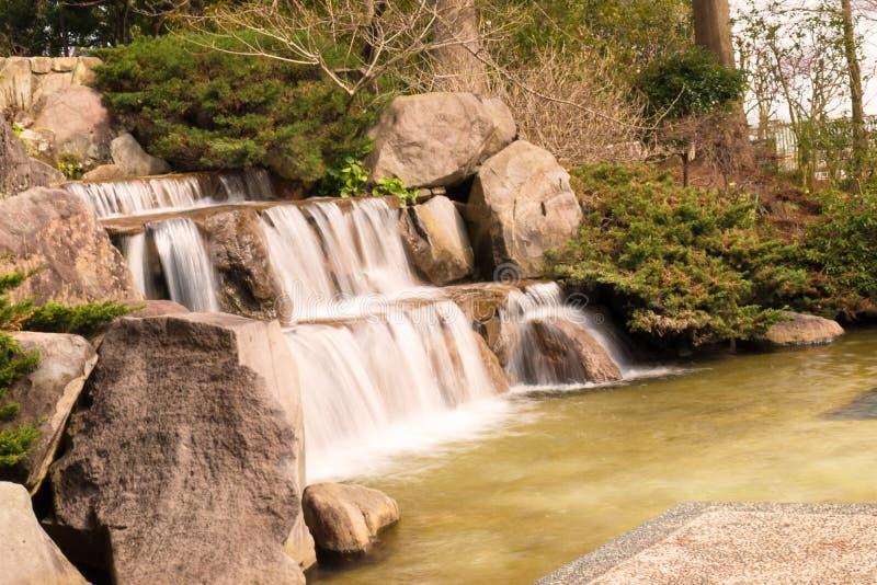 De Vijverbeek van de meerwaterval in Japanse tuin stock afbeelding