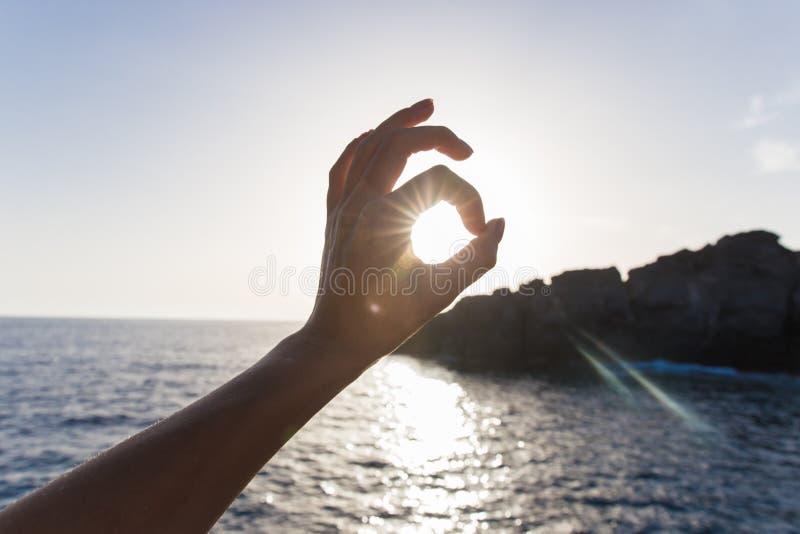 De vinger allen is goed op het overzees teken van goedkeuring handgebaren, zon in handen royalty-vrije stock foto's
