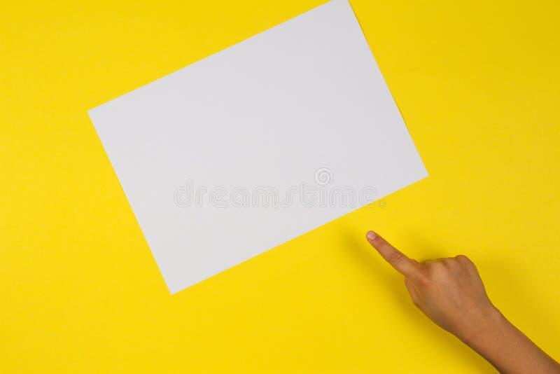 De vinger die van de jonge geitjeshand aan witte lege document kaart op gele achtergrond richten royalty-vrije stock foto