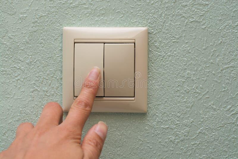De vinger drukt een elektronisch licht inschakelt een blauwe muurachtergrond royalty-vrije stock foto