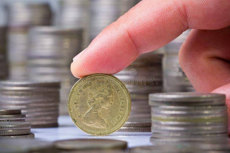 De vinger rolt een Brits pondmuntstuk royalty-vrije stock afbeeldingen