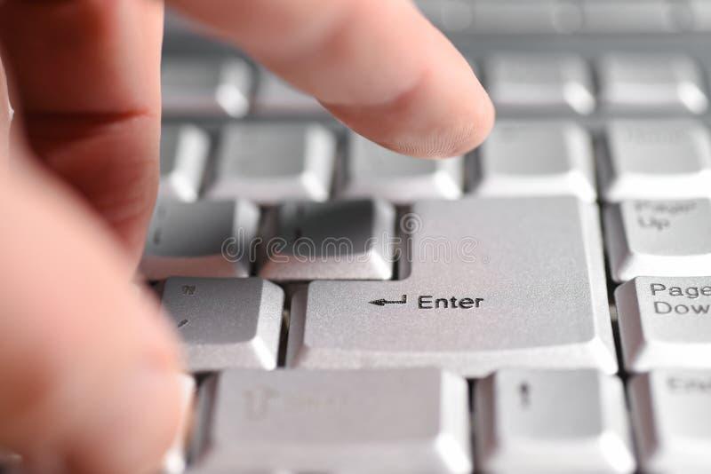 De vingerhand drukt de Enter knoop op het toetsenbord, close-up stock afbeelding