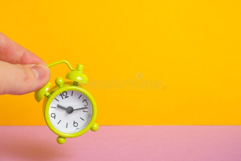 De vingers houden een uitstekende groene klok op een gele achtergrond stock foto's