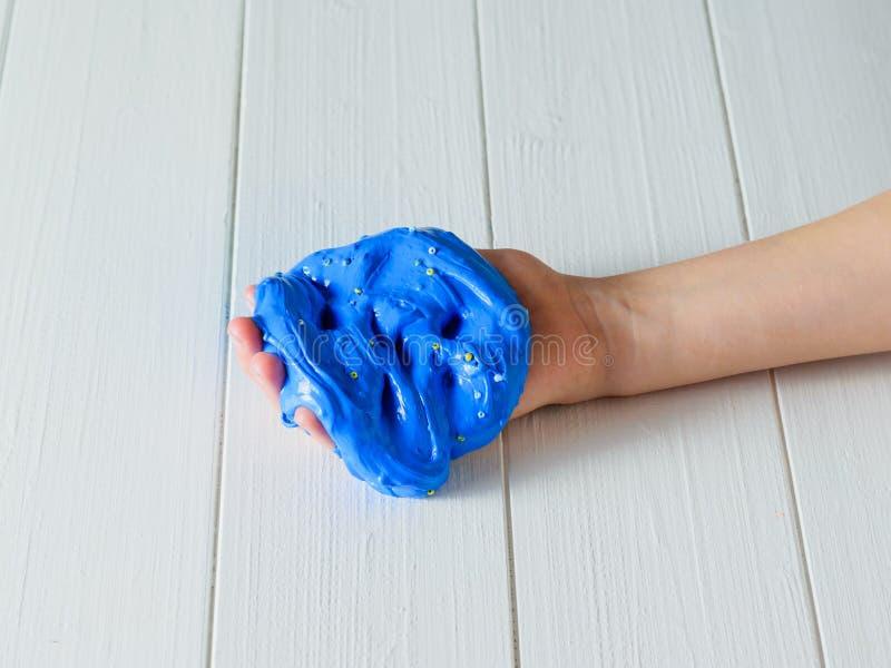 De vingers van het kind worden ondergedompeld in een blauw slijm op een witte houten lijst royalty-vrije stock afbeelding
