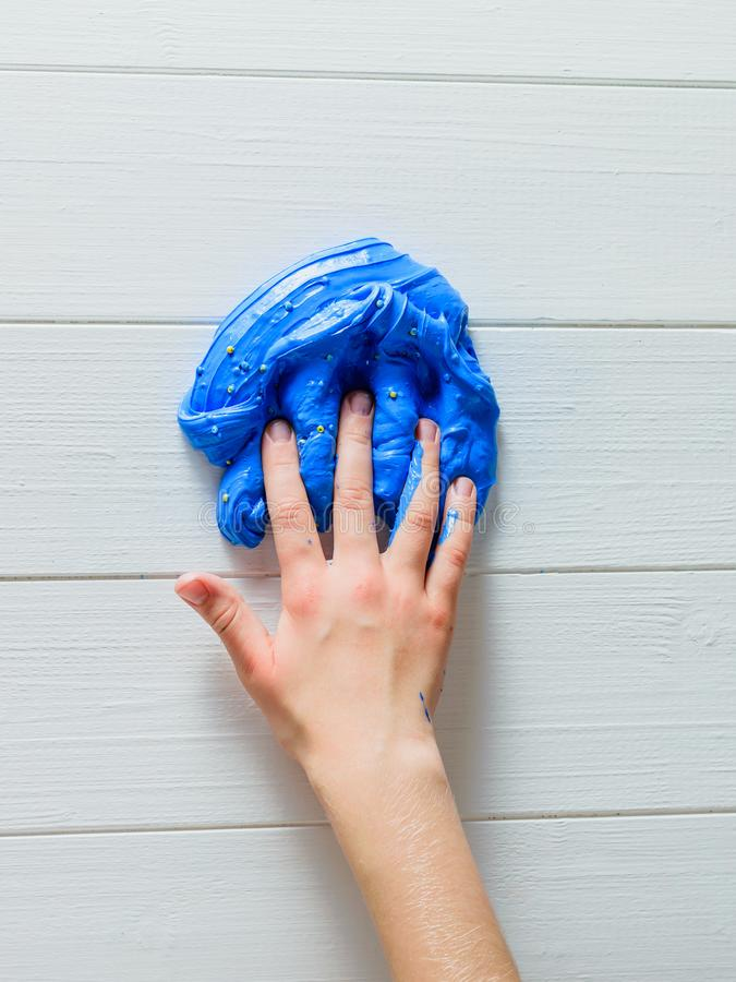 De vingers van het kind worden ondergedompeld in een blauw slijm op een witte lijst stock fotografie