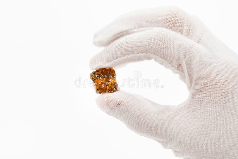 De vingers in witte handschoen houdt spessartinekristallen stock fotografie