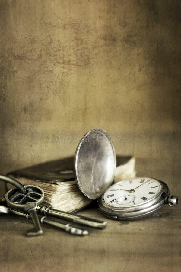 De vintage de grunge toujours la vie avec livre et le laiton K de montre de poche le vieux photographie stock