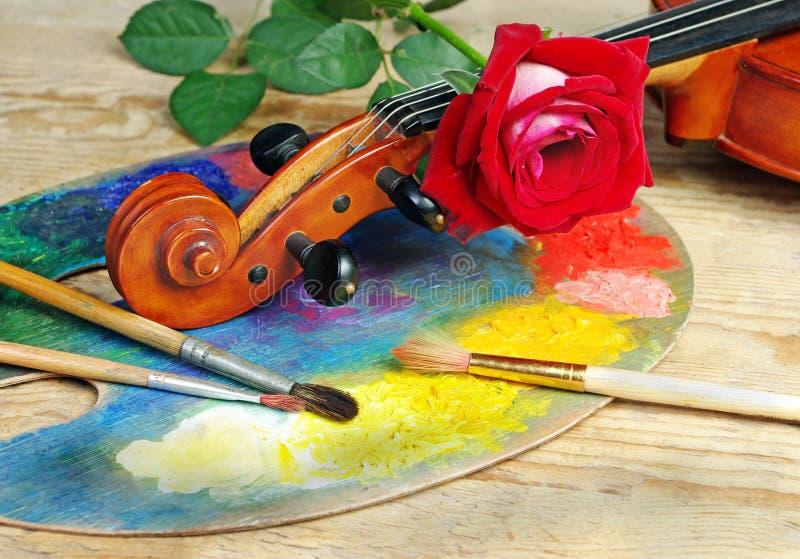 De viool, borstels, nam en palet op een houten achtergrond toe royalty-vrije stock foto's