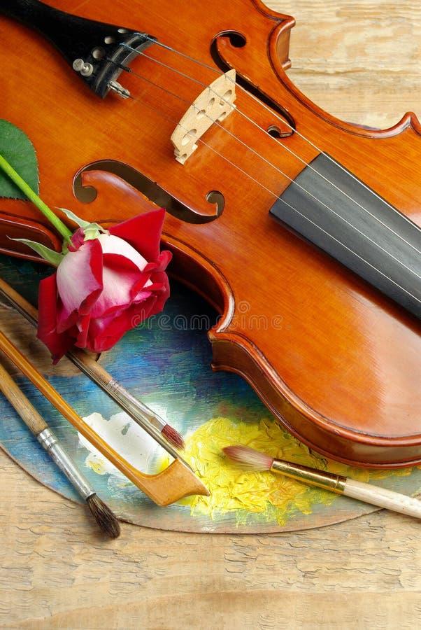 De viool, borstels, nam en palet op een houten achtergrond toe Hoogste mening royalty-vrije stock afbeelding