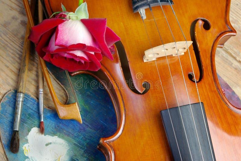 De viool, borstels, nam en palet op een houten achtergrond toe Hoogste mening stock fotografie
