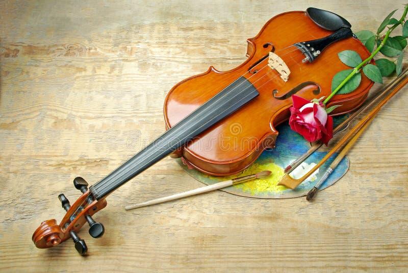 De viool, borstels, nam en palet op een houten achtergrond toe Hoogste mening royalty-vrije stock foto